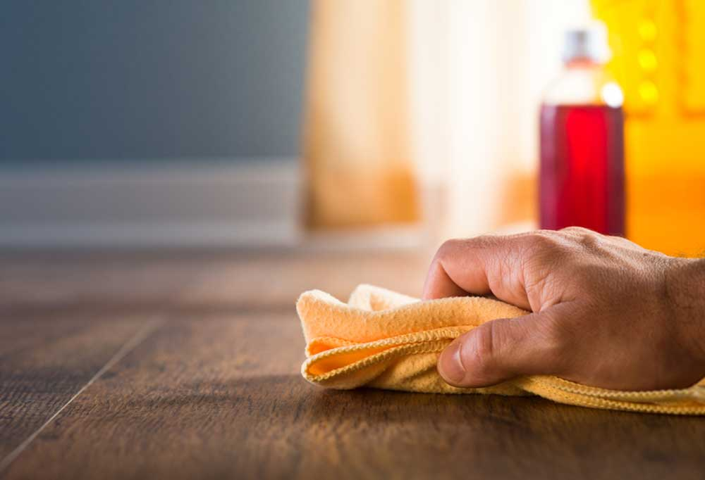 Man's hand with yellow rag wiping hardwood floor with cleaning liquid in the background