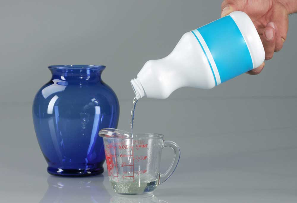 Bleach being poured into measuring cup with blue vase in background