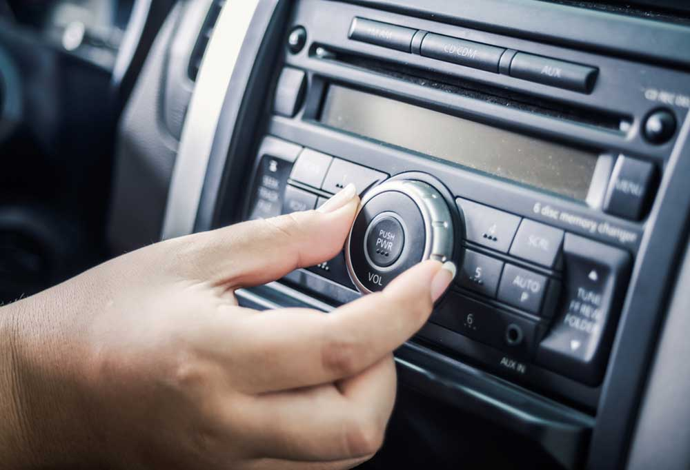 Hand turning the dial on a car radio