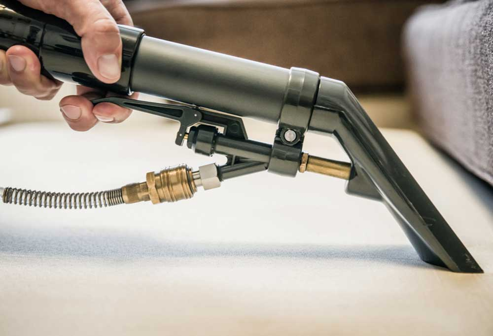 Close up of a cleaning wand on a carpet cleaner being used to clean carpet