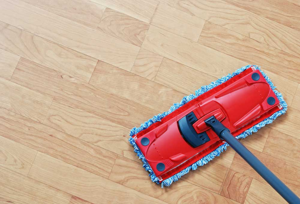 Red and blue dust mop on hard wood floor