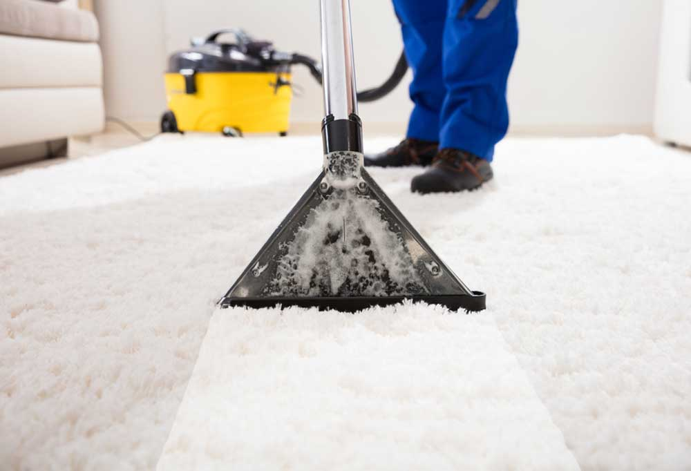 White carpet being cleaned with a carpet cleaner