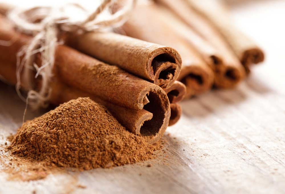 Cinnamon sticks and ground cinnamon on a wooden surface