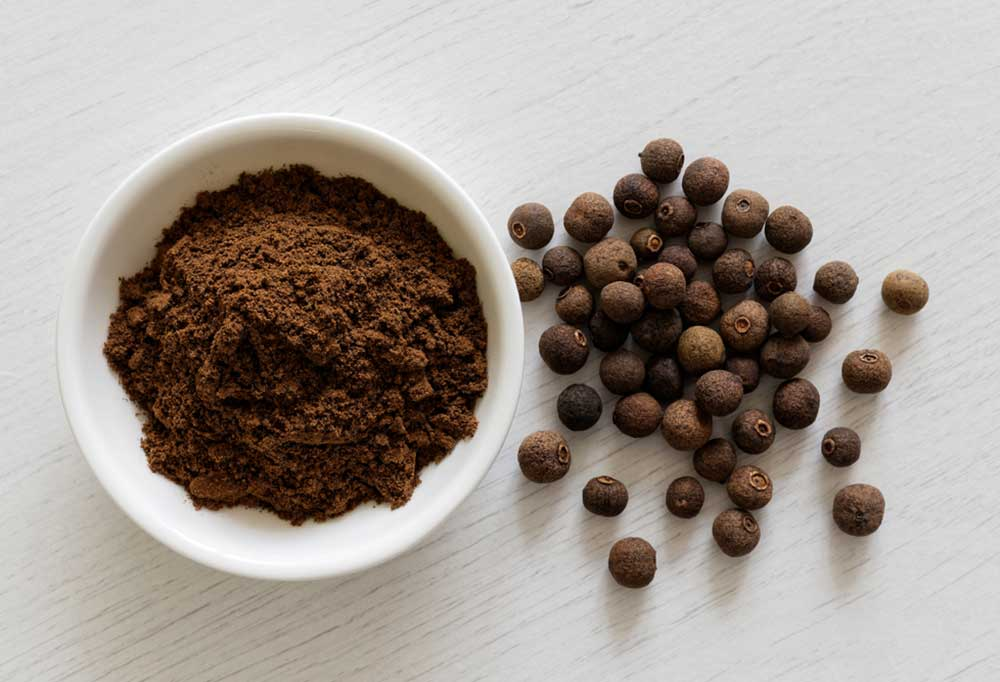 ground Allspice in a bowl and whole allspice on a wooden table