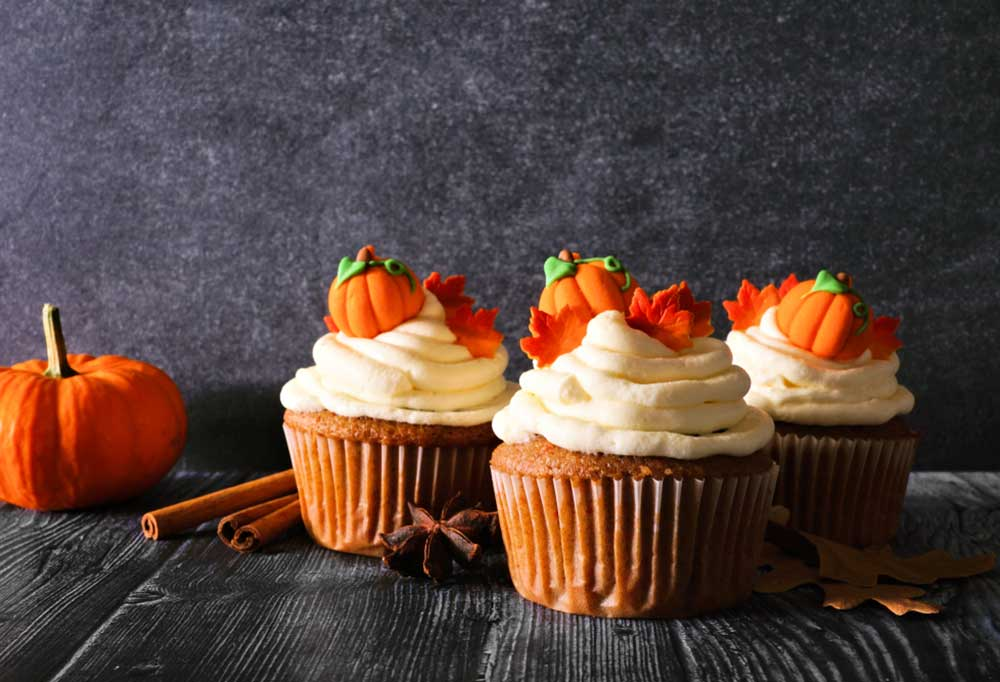 3 pumpkin cupcakes with tiny pumpkin and autumn leaf decorations on the icing