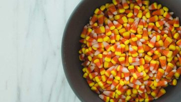 Candy Corn in a dark colored bowl on a marble counter
