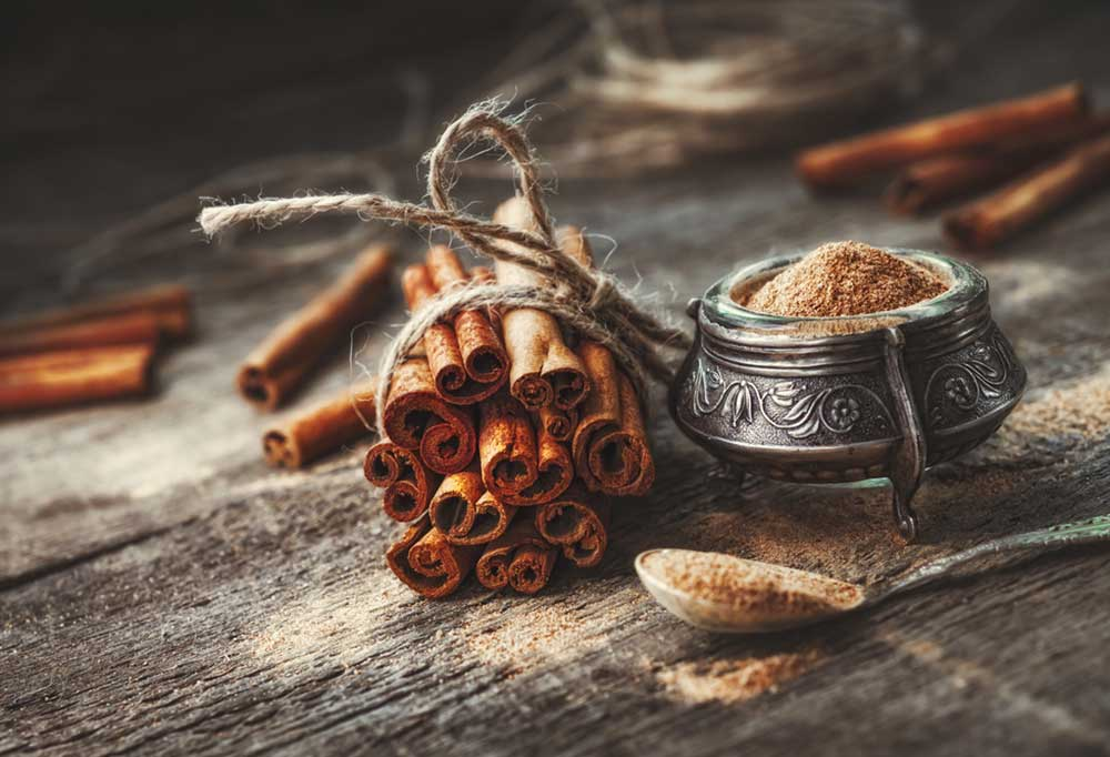bundle of cinnamon sticks next to a small silver bowl and spoon of ground cinnamon