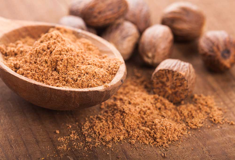 Whole and grated nutmeg on a wooden surface and in a wooden spoon