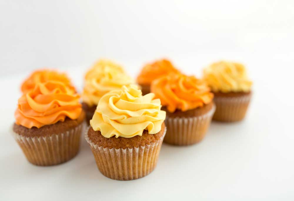 6 small cupcakes with yellow and orange frosting on a white background