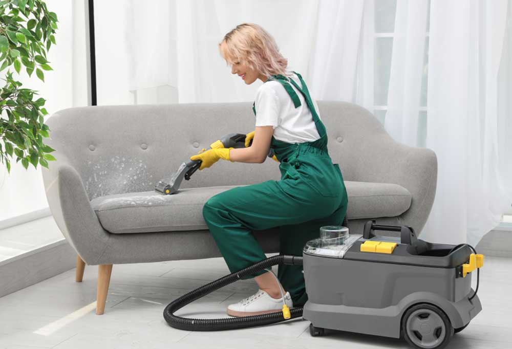 Woman in green overalls with a large upholstery cleaning machine, cleaning a light grey couch