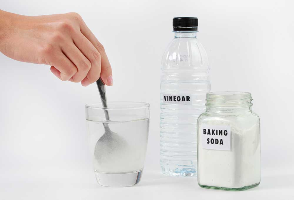 Vinegar and Baking soda in bottles with hand stirring a glass of vinegar and baking soda combined