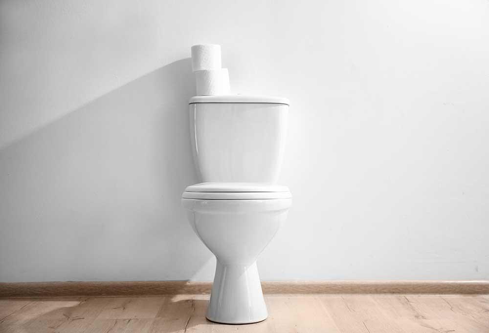 White toilet against a white wall on wooden fllors