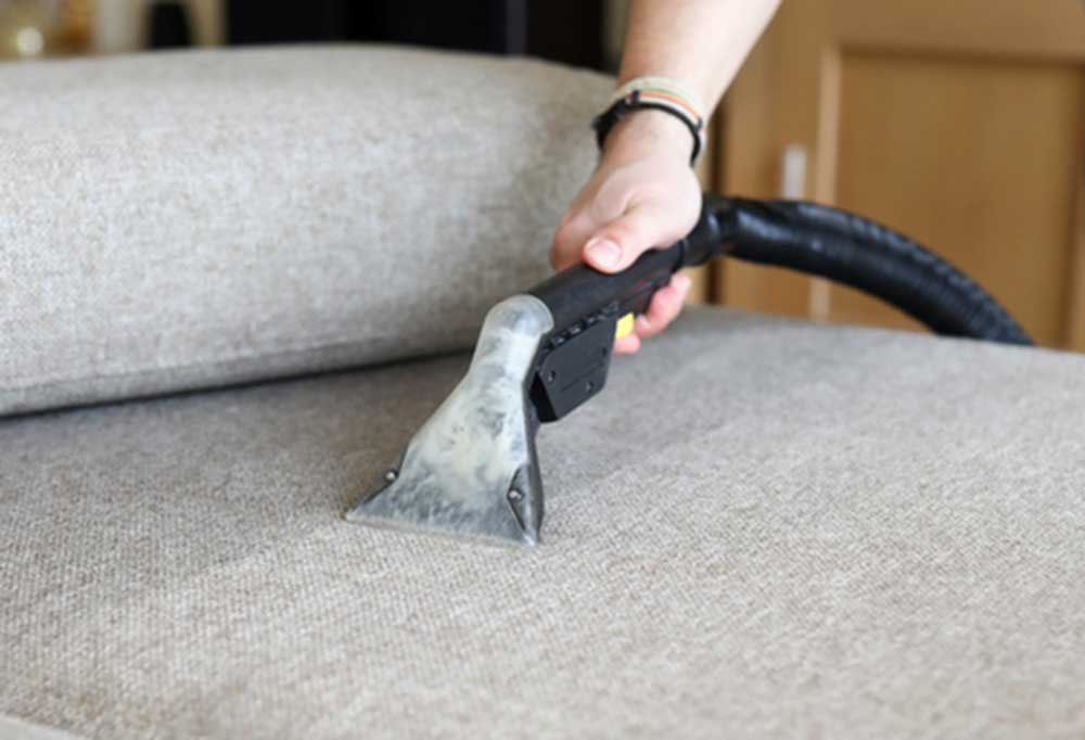 Person cleaning a couch with a spot cleaning machine