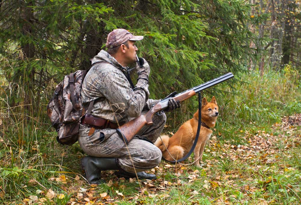 Hunter dressed in camouflage holding a riffle with a dog whistle in his mouth, kneeling next to his dog in the woods