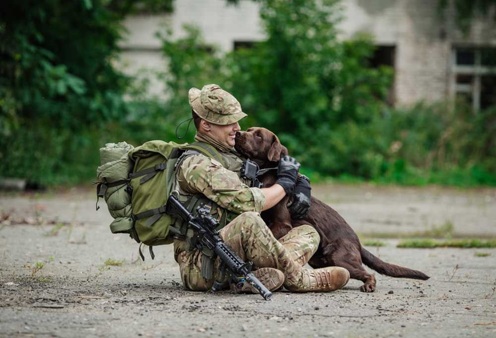 Man in military uniform on the ground outdoors hugging a chocolate Labrador retriever