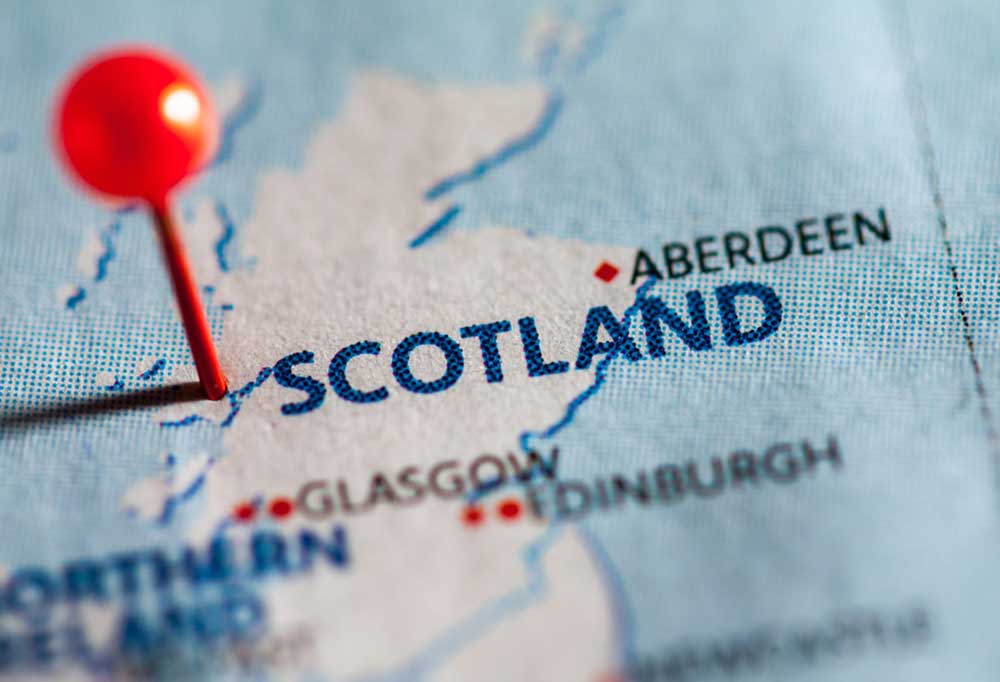 Blue map with a red pin sticking in Scotland