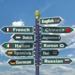 Directional signs on a pole that read ; English, Chinese, French , Dutch, Japanese, Italian, Korean, Spanish, Thai, German, Russian blue sky and clouds background