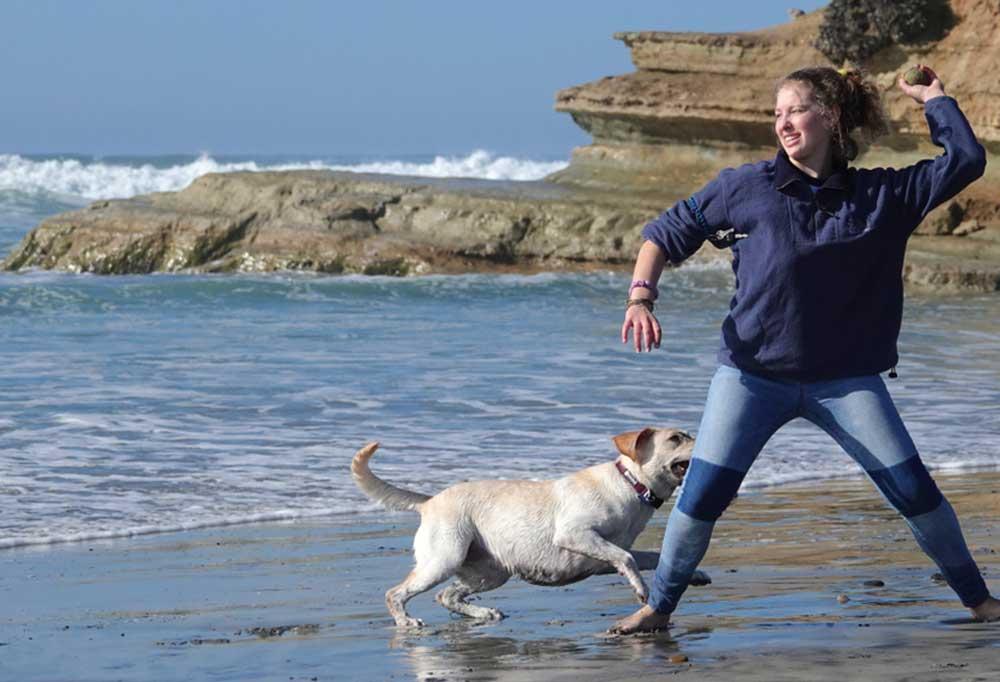 Woman throwing ball to a yellow Labrador retriever on a beach