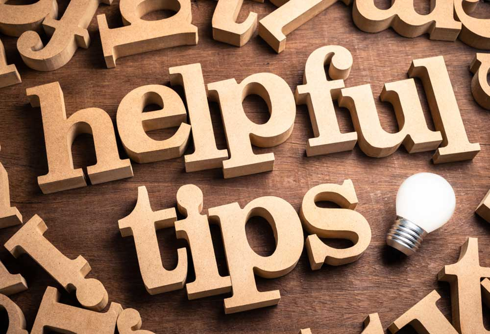 Wooden letters spelling Helpful Tips with a small lightbulb next to tips on a wooden background