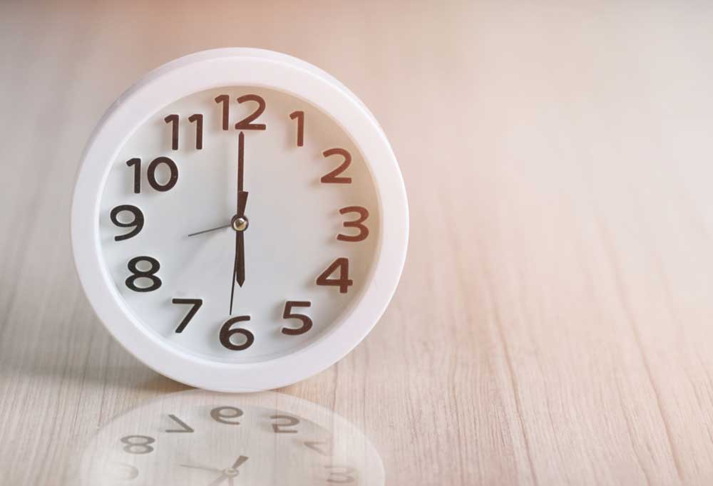 White alarm clock that reads 6 o'clock on a wooden table
