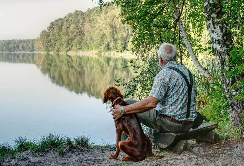 Older man in suspenders sitting on the bank of a river with his dog