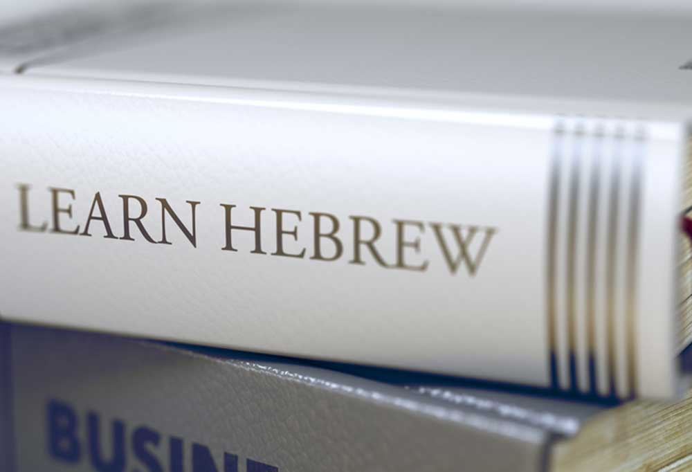 """Close up of 2 books stacked on top of each other. The top book reads """"Learn Hebrew"""""""