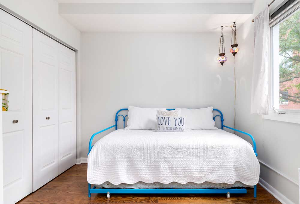 Blue iron bed with side rails.