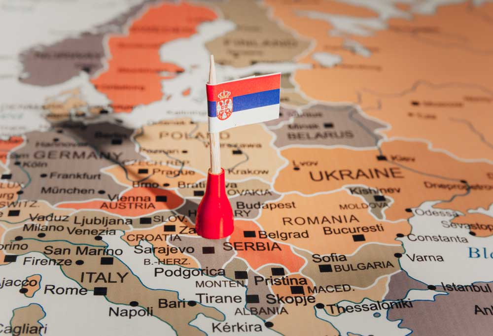 Orange  and brown color themed map of some of the Serbian speaking countries with a toothpick flag resting near Serbia.