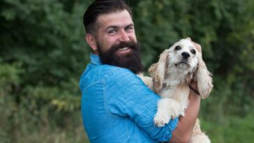 Man with dark hair, beard and mustache holding a cocker spaniel outdoors near the woods