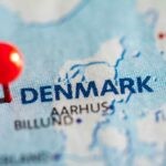 Blue and white map of Denmark with a red pin next to the word Denmark
