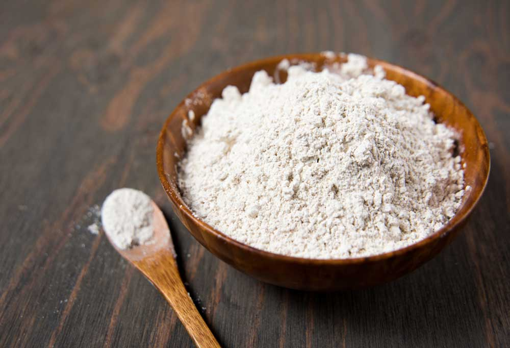 White powder in a wooden bowl on a wooden table next to a wooden spoon filled with white powder.