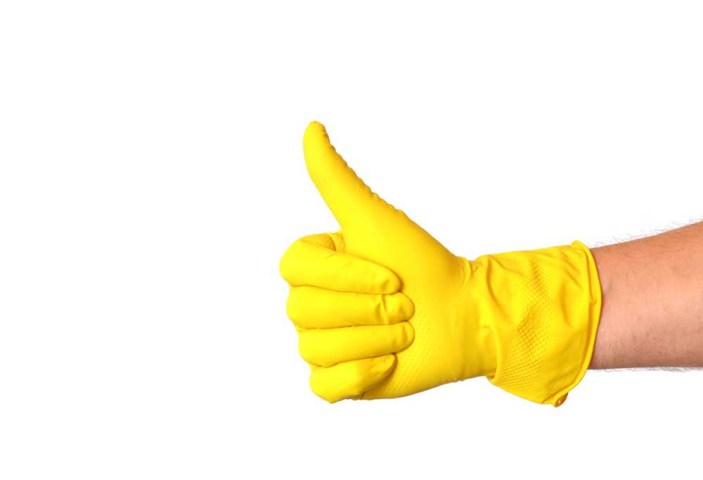Hand giving thumbs up wearing a yellow glove