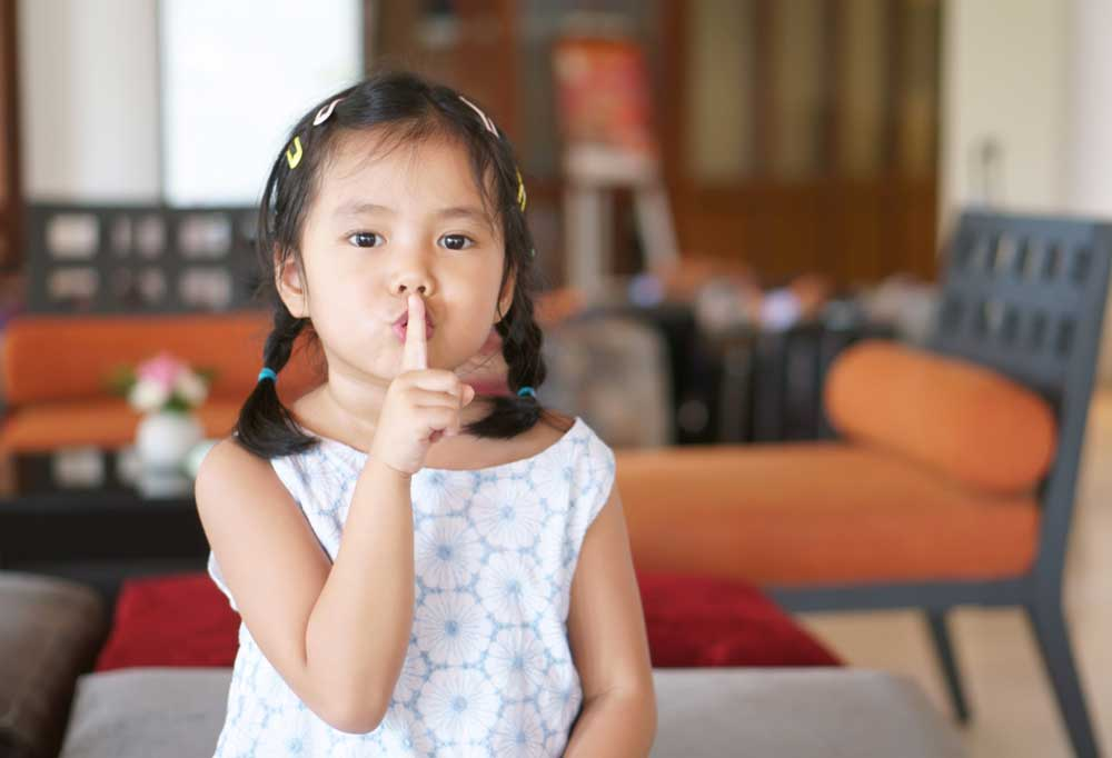 """Young girl in a family room setting, holding finger to lips as if saying """"Quiet"""""""