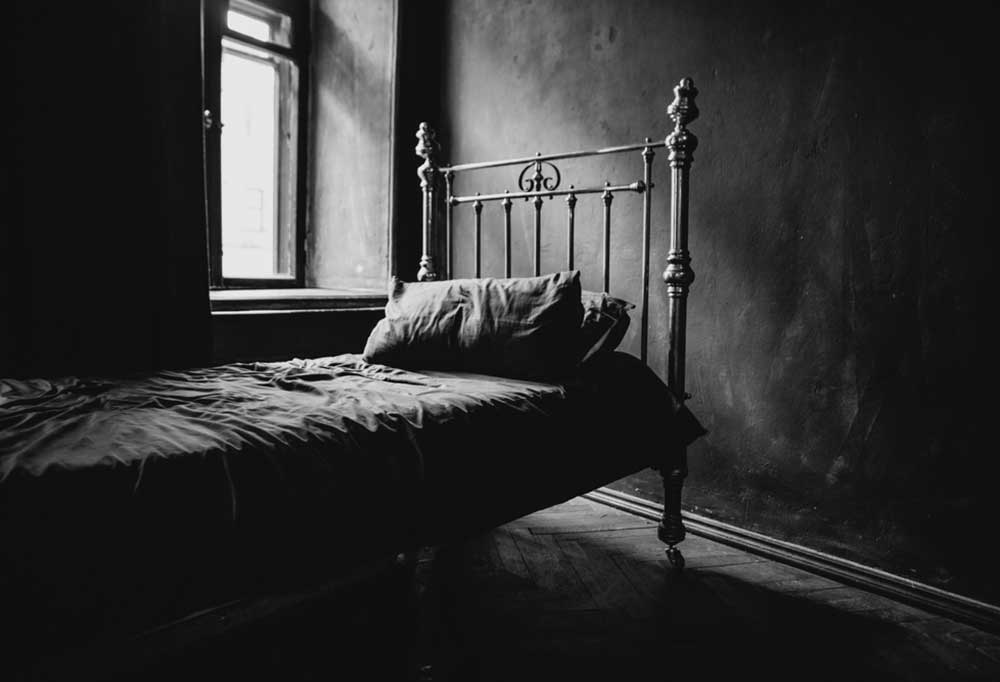 dark- black and white photo of an old iron bed next to a window