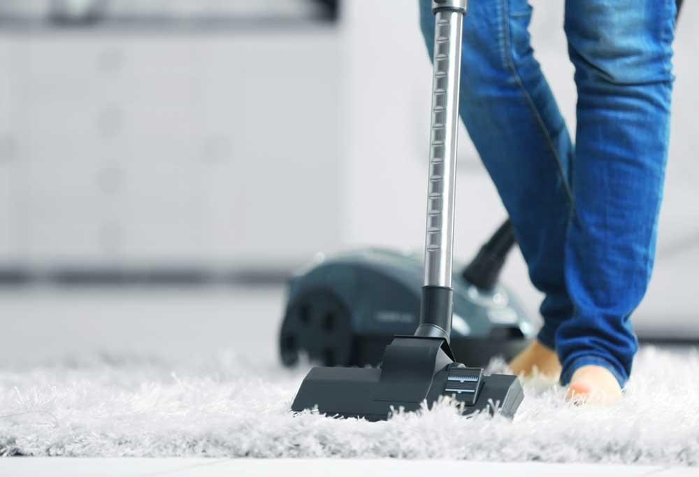 leg view of person vacuuming floor