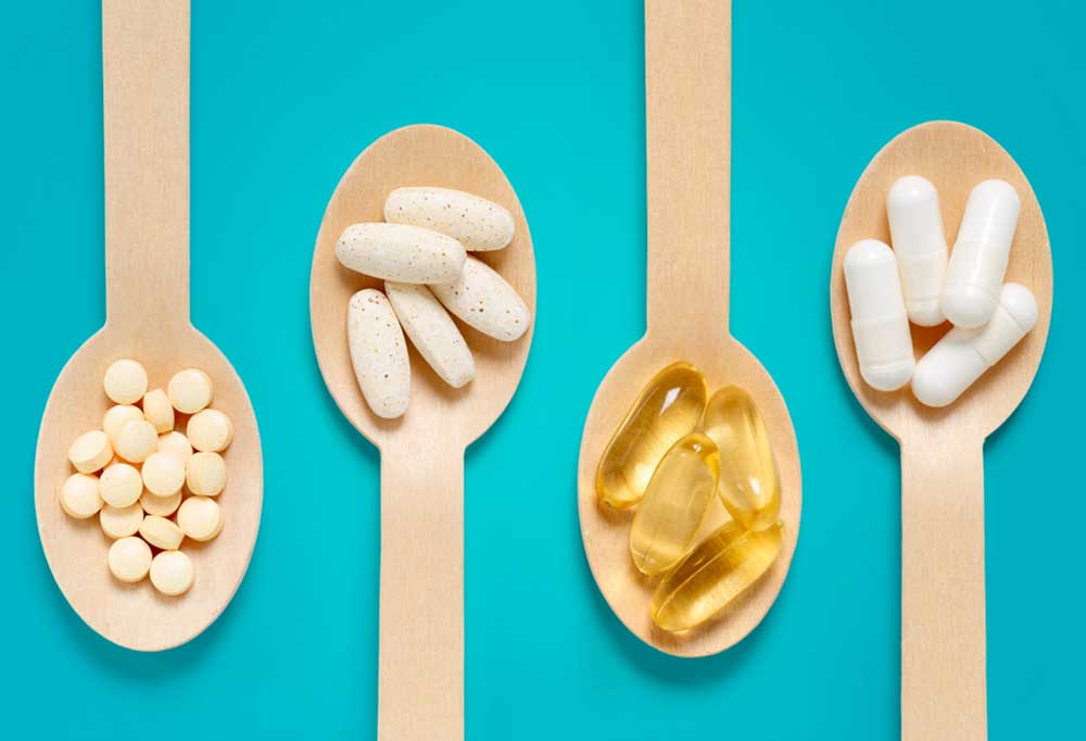 Vitamins and minerals on wooden spoons on a bright teal background
