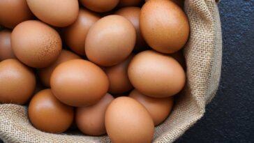 brown eggs resting in a burlap lines bowl on a black background