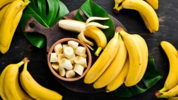 Sliced bananas in a bowl on a dark wood cutting board surrounded by while bananas in peels an banana leaves