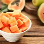papaya cubed in a white bowl on a wooden table surrounded by papaya cut into halves and quarters