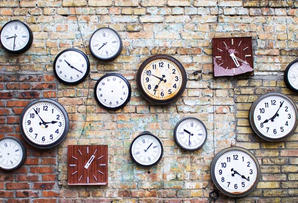 variety of different clocks on a rustic brick wall
