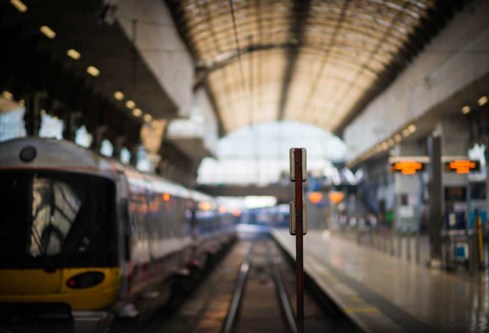 Blurred image of the rail system inside of a train station.