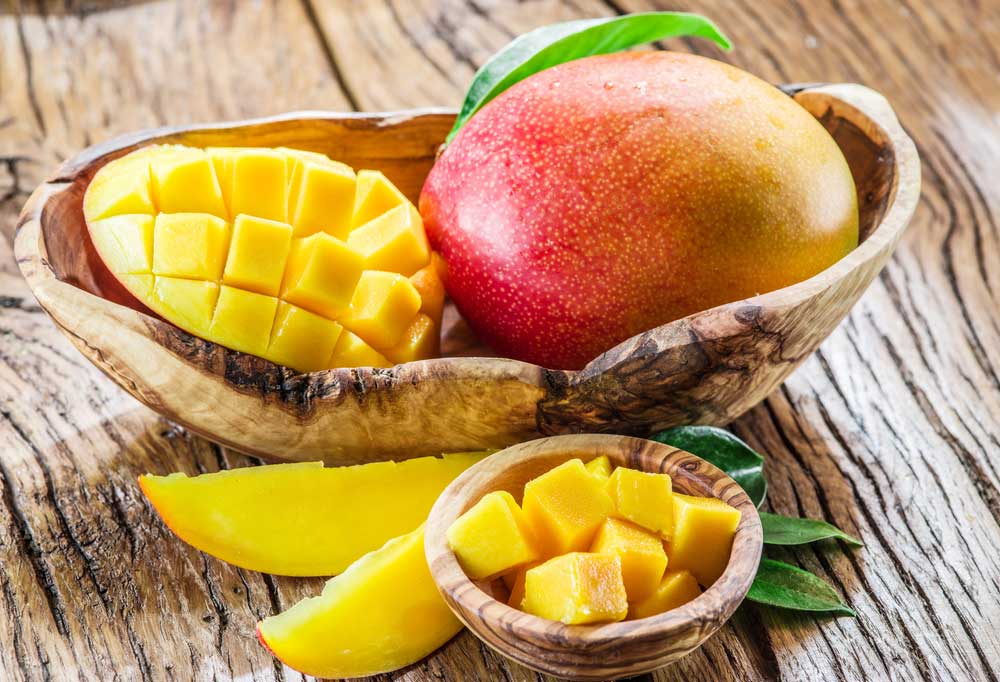 One whole mango and a sliced mango in a unique wooden bowl on a wooden table next to a small wooden bowl with chunks of mango.