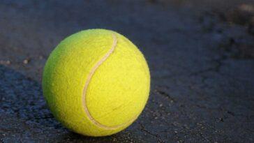 Single yellow tennis ball on back asphalt