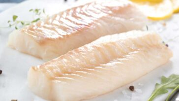 2 raw cod fish fillets on a white plate with seasoning and ganish
