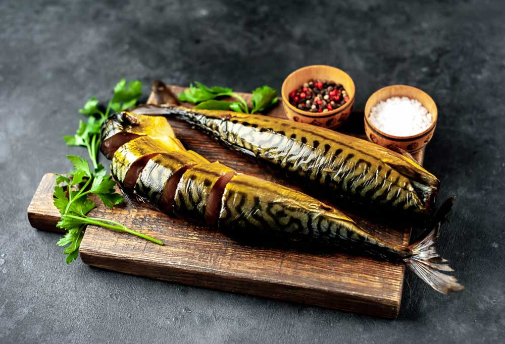 Atlantic Mackerel on as cutting board on a dark counter top with small bowls of seasonings