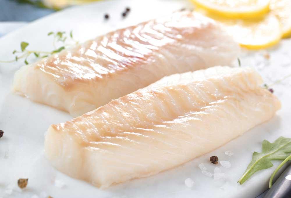 Cod fillets on a white plate with salt, pepper corns, lemon wedges and garnish