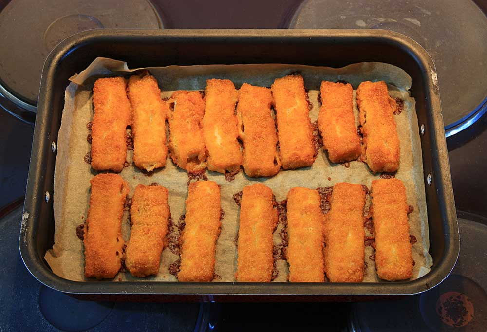 Cooked fish sticks on a parchment lined baking sheet