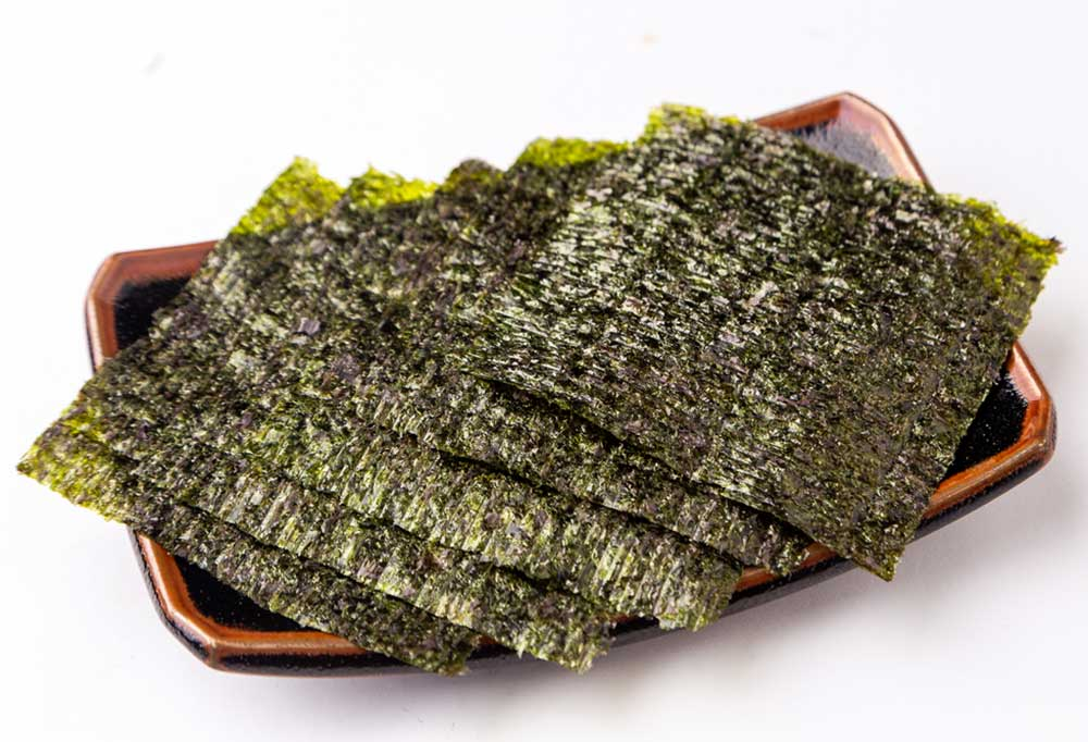 Sheets of seaweed on a rectangle stoneware plate on a white background.