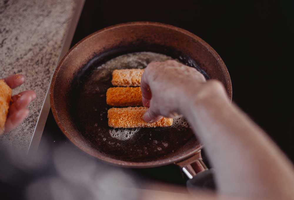 Person placing breaded fish sticks in a skillet with oil
