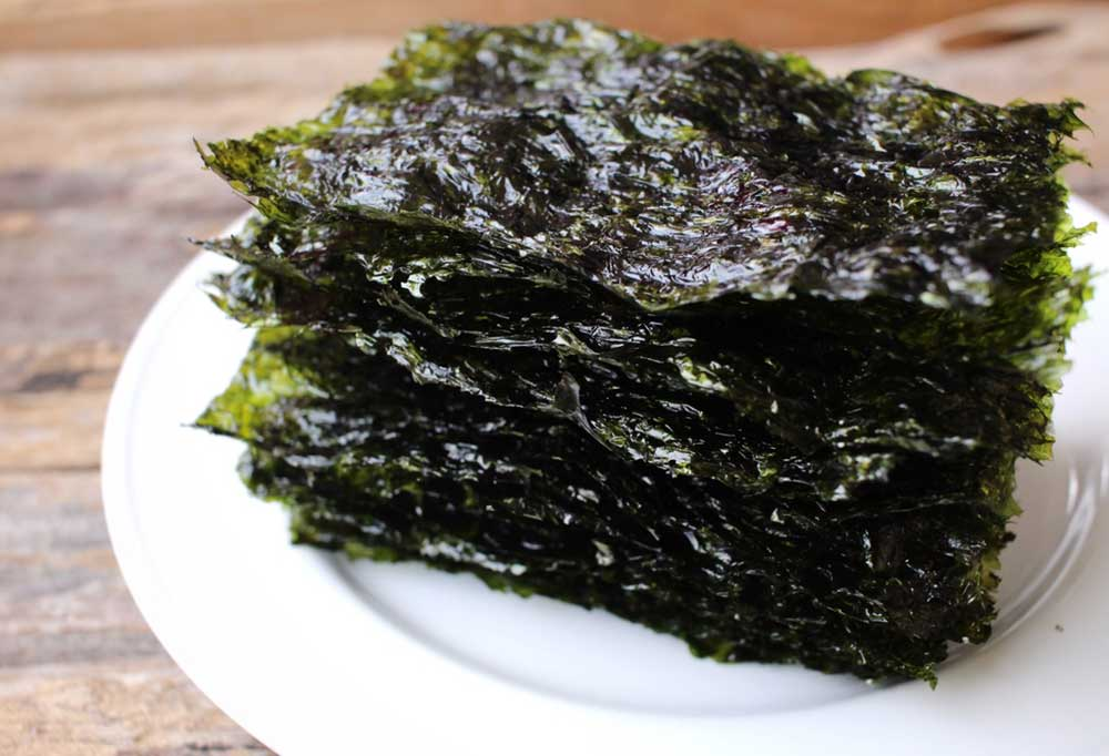 Sheets of nori on a white plate resting on a wooden table.